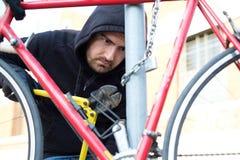 Tjuv som stjäler en parkerad cykel i stadsgata royaltyfri fotografi