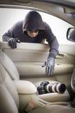 Tjuv som stjäler kameran från bilen royaltyfria foton