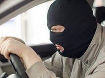 Tjuven i maskering stjäler bilen Arkivbild