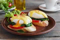 Tjuvjagade ägg benedict med spenat och tomaten Arkivbild