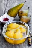Tjuvjagade päron med kryddor i sirap på den glass bunken Royaltyfri Foto