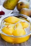 Tjuvjagade päron med kryddor i sirap på den glass bunken Arkivfoton