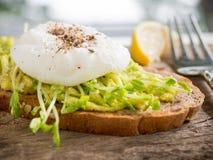 Tjuvjagat ägg och mosad avokado på helt veterostat bröd för sunt Fotografering för Bildbyråer