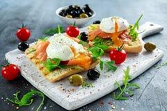 Tjuvjagat ägg på grillat rostat bröd med den rökte laxen, rucola, oliv och grönsaker på det vita brädet sund frukost royaltyfria bilder