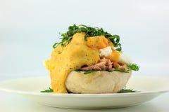 Tjuvjagat ägg på rostade engelska muffin, tonfisk och läcker buttery hollandaisesås med det Shiso bladet Royaltyfria Bilder