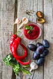 Tkemali sauce and ingredients. On rustic wood background Royalty Free Stock Images
