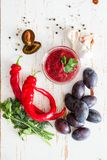 Tkemali sauce and ingredients. On white wood background Royalty Free Stock Images