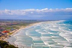 Tl-vågor på den Muizenberg stranden och den falska fjärden Royaltyfri Bild