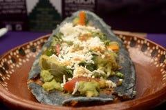 Tlacoyos messicani, un piatto fatto con cereale blu e riempito di fagioli fritti o di fave, simili al gordita messicano, con il g immagine stock libera da diritti
