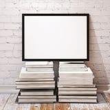 Åtlöje upp affischram på högen av böcker i vindinre Arkivfoton