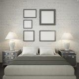 Åtlöje upp affischramar på den vita tegelstenväggen av sovrummet Royaltyfri Bild