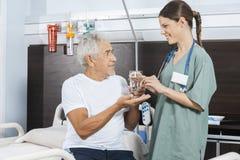 Tålmodigt hälerivattenexponeringsglas och preventivpiller från kvinnlig sjuksköterska Arkivbild