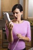 Téléphone de fixation de femme dans l'incrédulité Photo stock