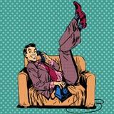 Téléphone parlant de sofa paresseux d'homme Photo stock