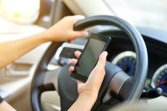 Téléphone portable d'utilisation de conducteur de femme conduisant la voiture Photographie stock libre de droits