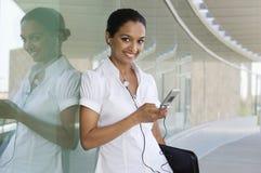 Téléphone portable de Listening Music On de femme d'affaires Photographie stock