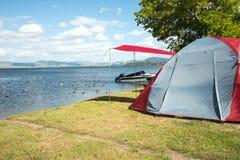Tält på en campa plats nära en sjö Royaltyfria Bilder