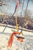 Töm gunga med snö och den rutiga halsduken Arkivbild