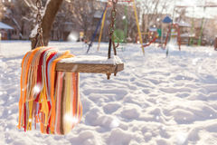 Töm gunga med snö och den rutiga halsduken Arkivfoton