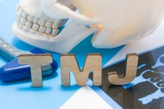 TMJ medical abbreviation of temporomandibular joint. TMJ letters surrounded by human skull with lower jaw, neurological hammer and royalty free stock photography