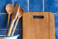 Tnąca deska, drewniane łyżki Retro styl, rocznik kuchni naczynia Dachówkowy błękit tło obrazy stock