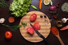 Tnąca deska, nóż, pokrojony pomidor i różnica warzywa, obrazy stock