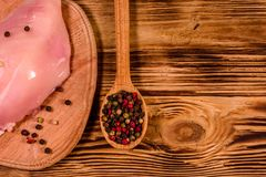Tnąca deska z surowym kurczakiem polędwicowym i łyżkowym z różnymi pikantność na drewnianym stole Odgórny widok zdjęcia royalty free
