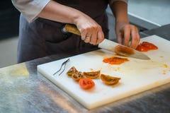 Tnący pomidory z kuchennym nożem chef Restauracja obrazy stock