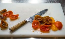 Tnący pomidory z kuchennym nożem chef Restauracja zdjęcia stock