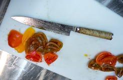 Tnący pomidory z kuchennym nożem chef Restauracja zdjęcie royalty free