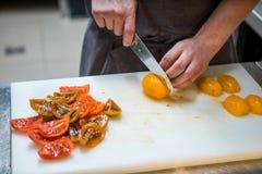 Tnący pomidory z kuchennym nożem chef Restauracja fotografia stock