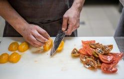 Tnący pomidory z kuchennym nożem chef Restauracja zdjęcia royalty free
