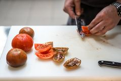 Tnący pomidory z kuchennym nożem chef Restauracja zdjęcie stock