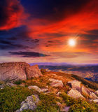 Tänd på stenberglutning med skogen på solnedgången Royaltyfria Foton