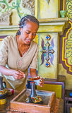 To add the coffee to Ethiopian jebena pot. KIEV, UKRAINE - JUNE 4, 2017: Ethiopian girl - the master of traditional historic coffee ceremony pours the coffee to Royalty Free Stock Photos