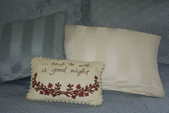 And To All A Goodnight Pillow. Pillows stacked on blue satin bed and pillow with message Royalty Free Stock Images