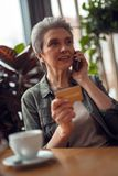Careful aged woman talking by phone in cafe. To be active and modern. Waist up portrait of smiling careful aged lady talking by mobile phone with credit card in stock photography
