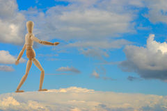 To be on cloud nine. Wooden figure in a walking pose, placed on a cloud, blue sky in background Royalty Free Stock Photography