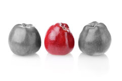 To be different bright one betwen colourless ones. Different bright red apple between two colourless apples on white background Royalty Free Stock Photo