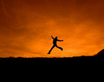 To be happy. Silhouette man jumping on orange sunset royalty free stock images