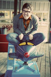 To be a kid again. Young trendy and handsome man laughing sitting in retro vintage airplane ride at penny arcade Stock Photography