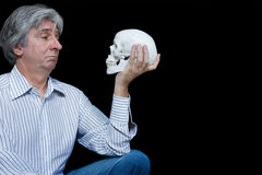 To be or not to be 2. Gray haired man staring at a skull Royalty Free Stock Photos