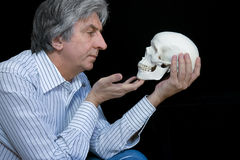To be or not to be. Gray haired man looking at a skull Stock Photo