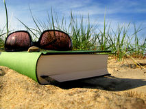 To be on vacation. Relaxing day on the beach with a book and shades Stock Photography