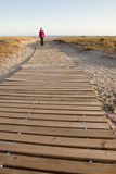 To the beach. Woman wearing a wind coat walking on a wooden path that goes to a beach next to the sea. The picture was taken in the south of Spain (Andalusia) Stock Image