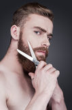 To beard or not to beard. Portrait of handsome young shirtless man cutting his beard with scissors and looking at camera while standing against grey background stock photography