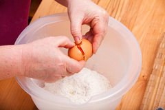 To break an egg into the cake dough Stock Photos