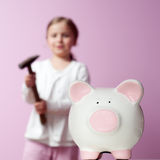 To break piggy bank. Little girl with hammer and piggy bank Royalty Free Stock Photo