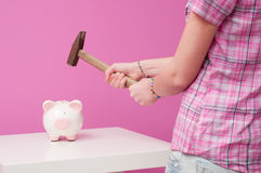 To break piggy bank. Young girl wants to break piggy bank Royalty Free Stock Image