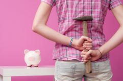 To break piggy bank. Young girl with hammer and piggy-bank Royalty Free Stock Photography